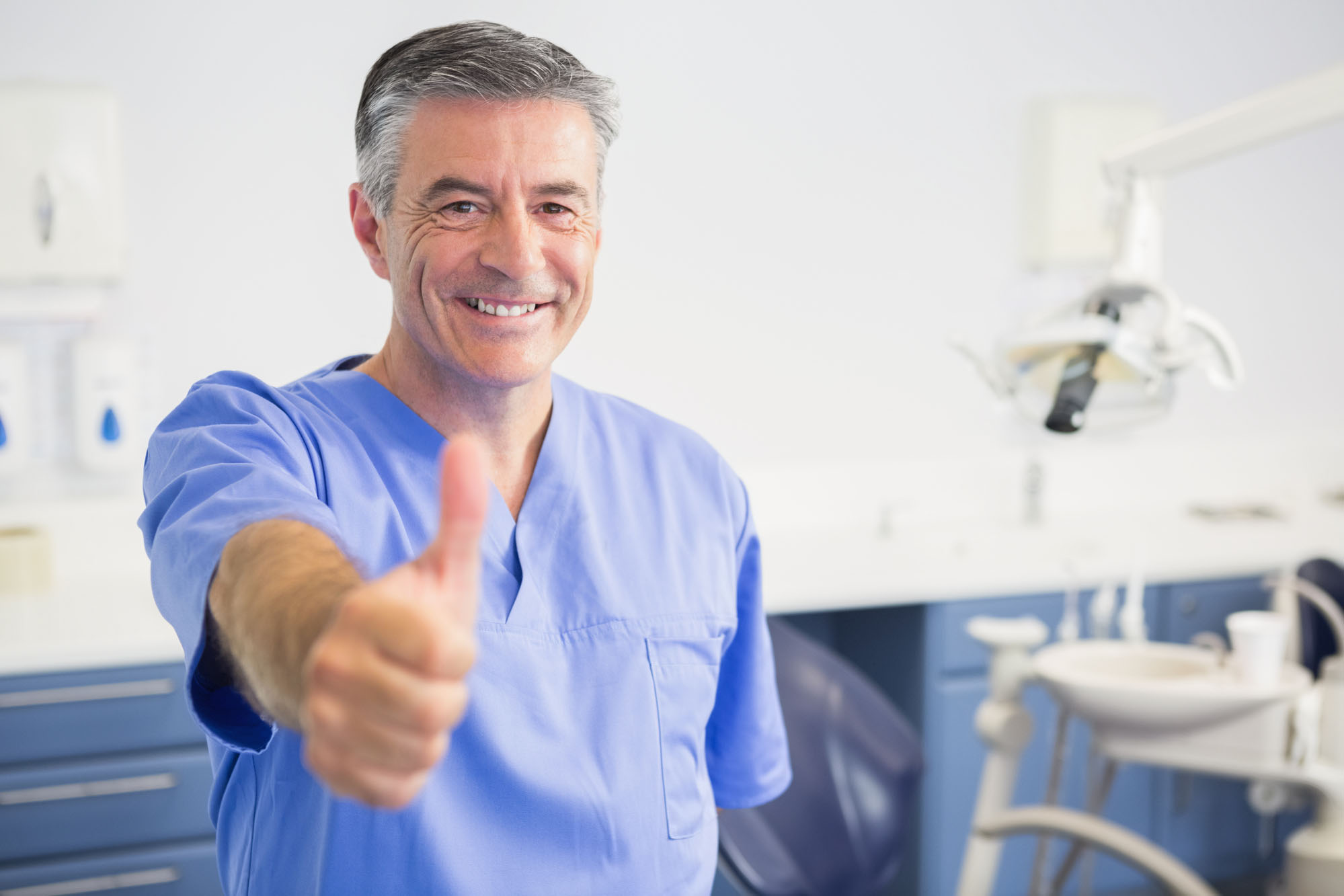 Portrait of happy dentist with thumbs up in dental clinic